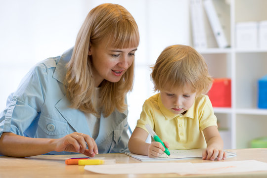 Cute child boy drawing and writing with colorful markers pens at kindergarten. Creative kid painting at playschool. Teacher helps to little pupil.