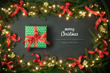 Merry Christmas and happy new year greetings in vertical top view dark blackboard with pine branches,ribbons, lights decorated frame and gift present box.Xmas winter holiday season social media card