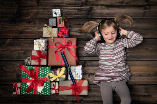 Happy smiling child girl in homewear listening music in vertical top view vintage wood with christmas tree pine made of gift present boxes.Xmas winter holiday season party social media card background