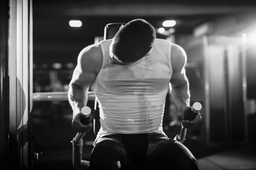 Close up of young caucasian man doing strength exercises on exercise equipment. Black and white portrait, gym interior.