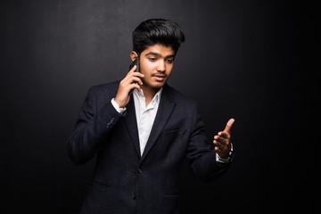 Indian man talking on phone on black background