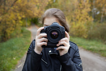 young girl in a leather jacket looks into SLR camera, ready to take a picture of a beautiful staged advertising, portrait, or reportage frame, against a blurred asphalt road, and autumn alley of trees