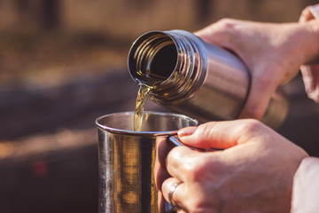 Woman pours hot tea out of thermos into metal cup in autumn forest