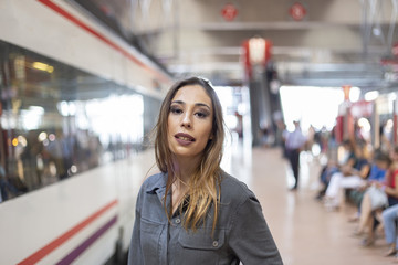 Confident female standing on railway station