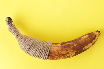Blackened banana tied with twine. Banana on yellow background. Spoiled tropical fruit in pop art style. Fruit concept. Source of food poisoning