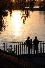 A couple with a child admires the sunset on the river. Silhouette.