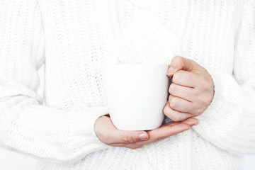 Closeup of woman's hands in white knitted sweater holding cup of coffee. Blank mug mock-up scene. Chritsmas winter design. Feminine styled stock photo.
