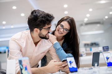 Man and woman talking about which smart phone to buy. Man holding in hands smart phone while woman leaning on him.