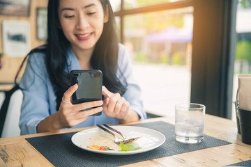 Beautiful young woman using an application to send an sms message in her smartphone at restaurant.
