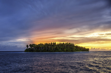 Scenic view of island amidst sea against dramatic sky during sunset