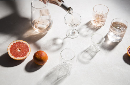 High angle view of drink pouring in glasses by citrus fruits on table