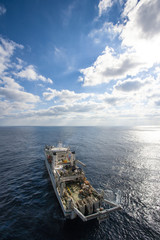 High angle view of drill ship on sea against cloudy sky