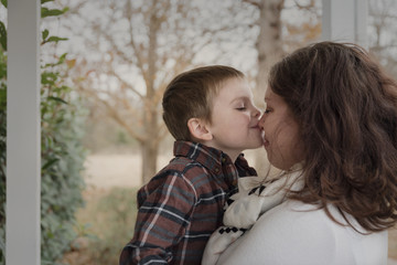 Close-up of son kissing mother on nose against trees in porch
