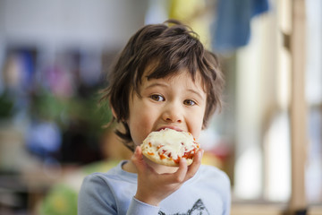 Portrait of boy eating pizza muffin in cafe