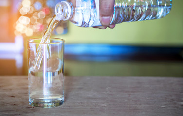Pouring purified fresh drink water from bottle on glass table background