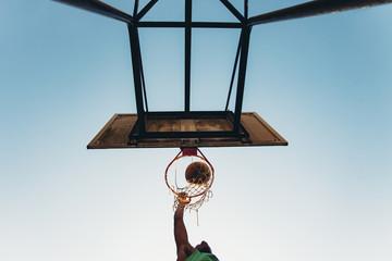 Man making basket with basketball