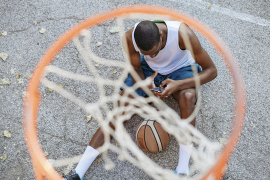 Man with basketball using smart phone
