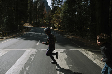 Side view of siblings running on road at Yosemite National Park during sunny day