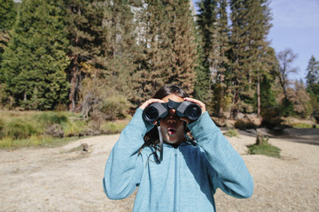 Surprised girl using binoculars while standing in forest at Yosemite National Park