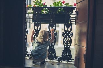 Little toddler playing on the balcony