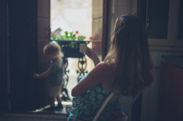 Mother watching her toddler by balcony