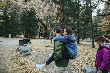 Side view of father piggybacking daughter while girl walking in forest at Yosemite National Park