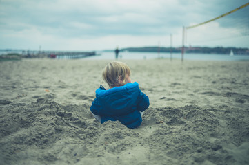 Little toddler on the beach in autumn