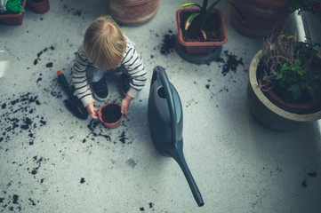 Toddler playing with dirt and watering can