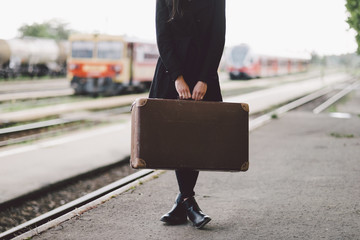 Low section of woman carrying suitcase while standing on railroad station platform
