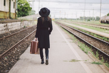 Rear view of woman carrying suitcase while walking on railroad station platform against sky