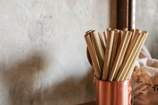 Close up of natural color bamboo straws in rose gold bronze cup  with loft concrete background
