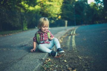Toddler sitting on the sidewalk in park