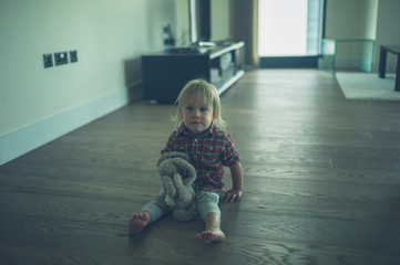 Little toddler in city apartment with toy bear