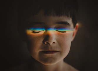 Close-up of cute boy with spectrum on closed eyes in darkroom at home