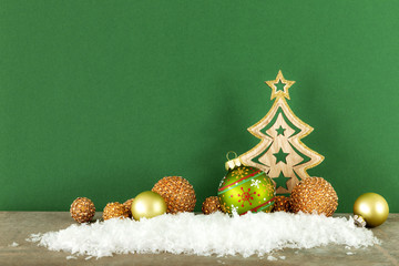 Christmas decoration green background with wooden tree glass balls and snow