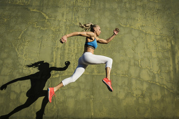 Low angle view of muscular woman leaping against green wall during sunny day