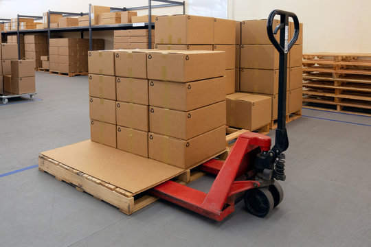 Pallet Jack with full of cartons at logistics warehouse