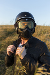 Male biker fastening helmet while standing amidst plants against clear blue sky during sunset