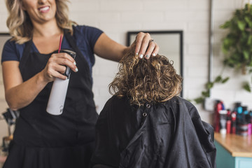 Midsection of hairdresser spraying water on girl's hair in salon