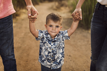 Portrait of cute son holding hands of parents while walking on field