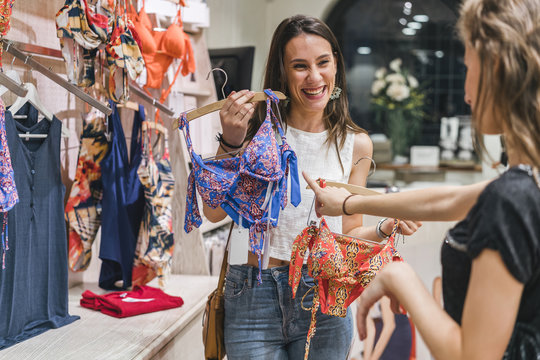 Happy female friends buying lingerie in store