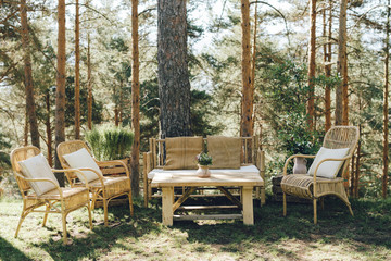 Decorative vintage wedding table, couch and chairs to rest in a pinetree forest