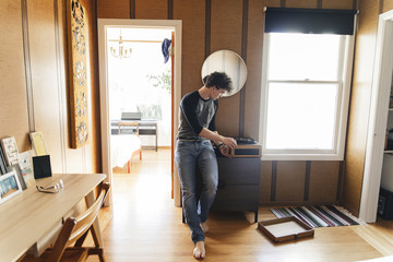 Man playing record player while sanding at home