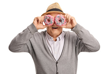 Mature man holding donuts in front of his eyes