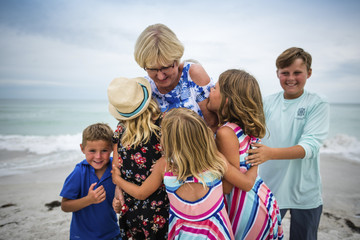 Grandchildren embracing grandmother at beach