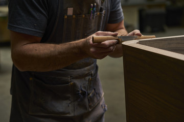 Midsection of carpenter shaping wood with work tool in workshop