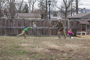 Father playing with children in backyard