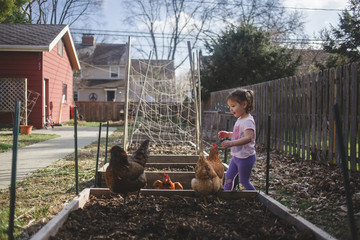 Cute girl with hens at garden