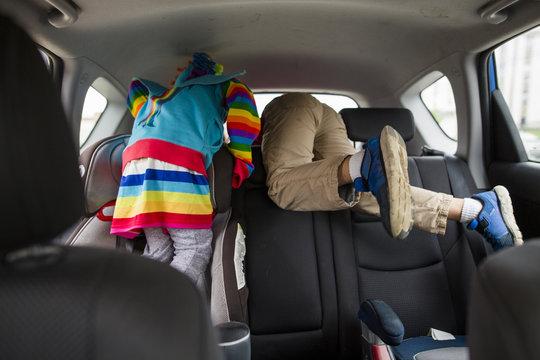 Siblings playing in car