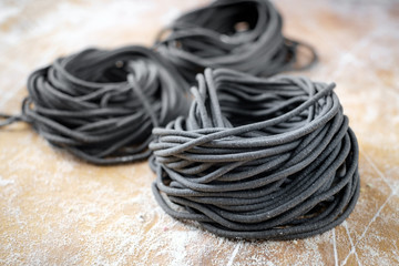 Raw uncooked black spaghetti pasta homemade on a rustic wooden board
